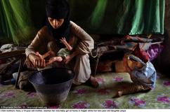 Asia, en 14-årig mamma, tvättar sin nya lilla flicka hemma i Hajjah medan hennes två-åriga dotter leker.