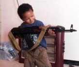 Khadijah Dare's young son poses with an AK-47rifle. This is a story that begins in the streets of Lewisham and ends in the heat of the Syrian desert, on the front line of the holy war for an Islamic caliphate. Among the British Muslims living in Syria and Iraq alongside terrorist super-group Isis, one figure has attracted particular attention recently Ñ a mysterious woman using the Twitter name Muhajirah fi Sham (meaning Òimmigrant in SyriaÓ), posting pictures of her young son holding a AK-47. She has described witnessing the execution of a young ÒrapistÓ in the Syrian town where she lives with her fighter husband and has called on Londoners to join her.