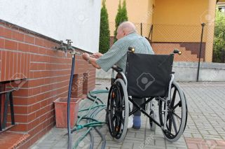 13818524-old-man-in-a-wheelchair-working-on-his-house-stock-photo