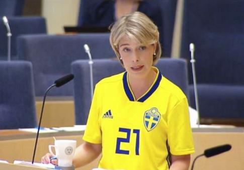 Strandhäll i riksdagen, klädd i landslagströja för att en fotbollsspelare utsatts för en fejkad rasistattack. Hon borde stå där i en blodig sjukhusrock.